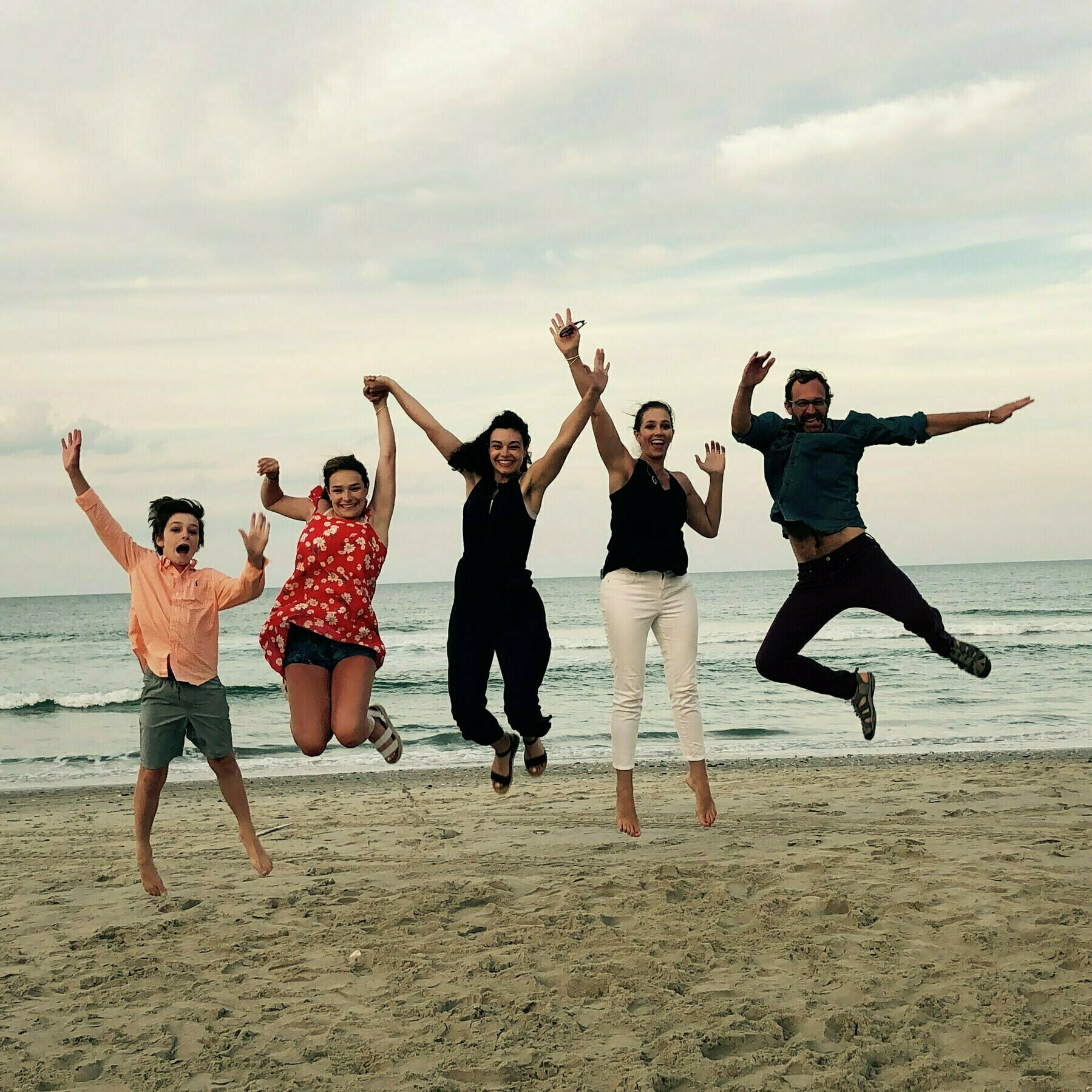 Zuiker Family jumping at the beach